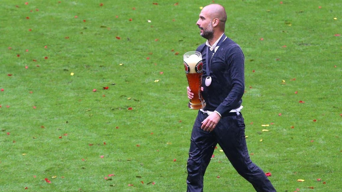 Munich coach Pep Guardiola walks with a beer mug as Bayern Munich's soccer team celebrates the German Championships during celebrations in the stadium in Munich, Germany, Saturday May 14, 2016. (Karl-Josef Hildenbrand/dpa via AP)