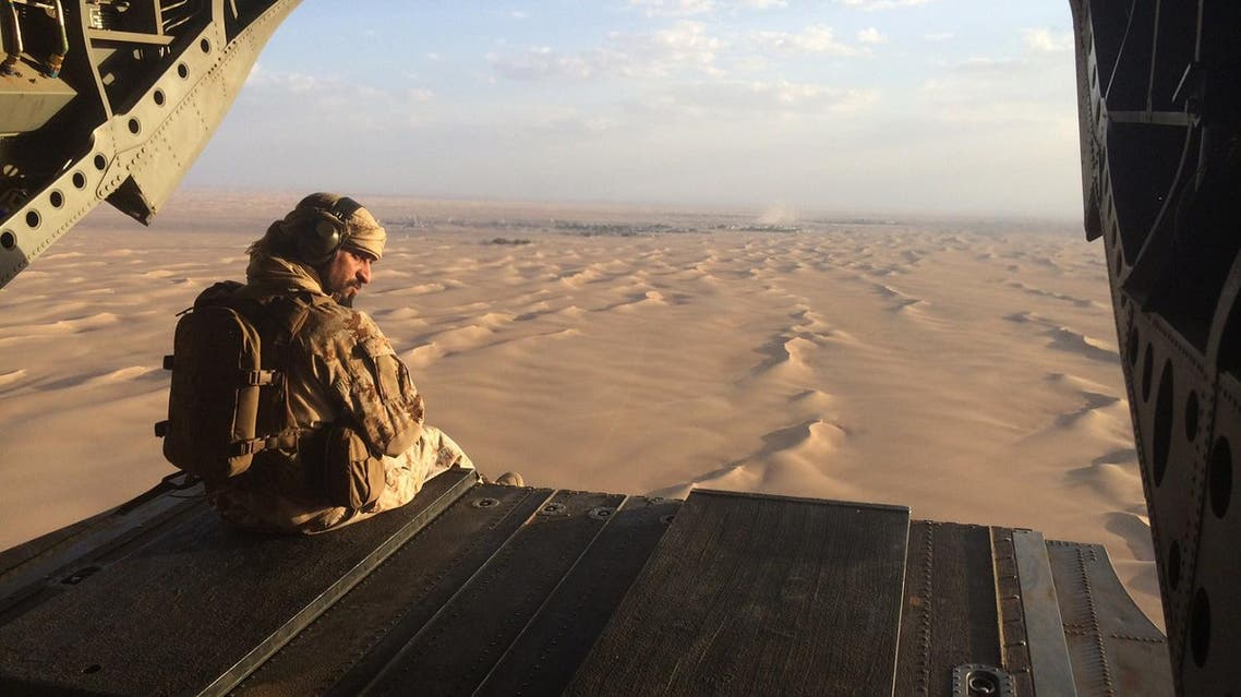 In this Sept. 17, 2015 photo, an Emirati gunner watches for enemy fire from the rear gate of a United Arab Emirates Chinook military helicopter flying over Yemen. The United Arab Emirates is taking part in regional conflicts and likely has spent into the billions of dollars to support its military in 2015 as well, a new report revealed. Both the UAE and Saudi Arabia also sent troops into Bahrain to put down its 2011 Arab Spring-inspired protests. (AP Photo/Adam Schreck, File)