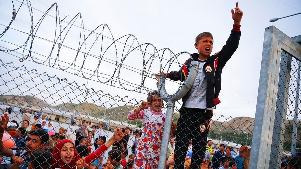 Refugee youths gesture from behind a fence as German Chancellor Angela Merkel, Turkish Prime Minister Ahmet Davutoglu, EU Council President Donald Tusk and European Commission Vice-President Frans Timmermans (all not pictured) arrive at Nizip refugee camp near Gaziantep, Turkey, April 23, 2016. REUTERS