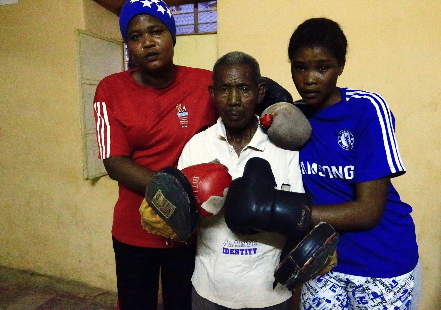 Sahar Mohamed Al Dooma (L) and Saraa Mutawkil (R) take a group photo with coach Ali Al-Aqraa after boxing practice at Al Rabie club in Omdurman May 10, 2016. REUTERS