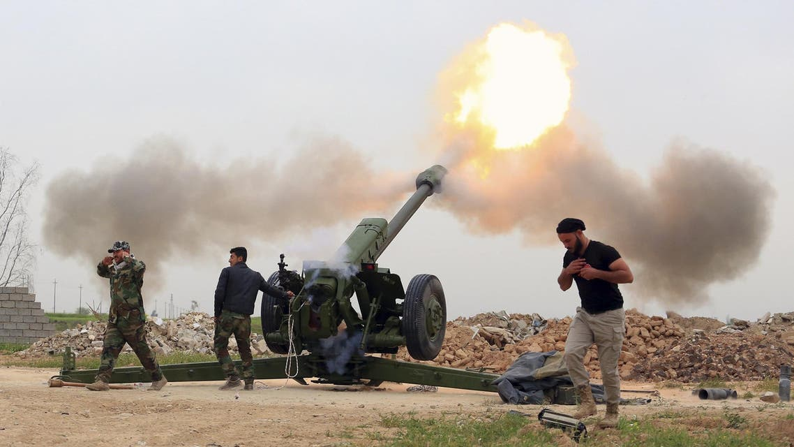 In this Saturday, March 26, 2016 photo, Iraqi security forces fire at Islamic State militants positions from villages south of the Islamic State group-held city of Mosul, Iraq.