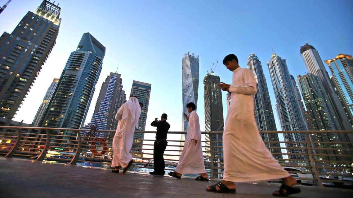In this April 1, 2015 photo, Gulf Arab visitors in their traditional Kandora pass by giant skyscrapers at the Marina waterfront in Dubai, United Arab Emirates. (AP)
