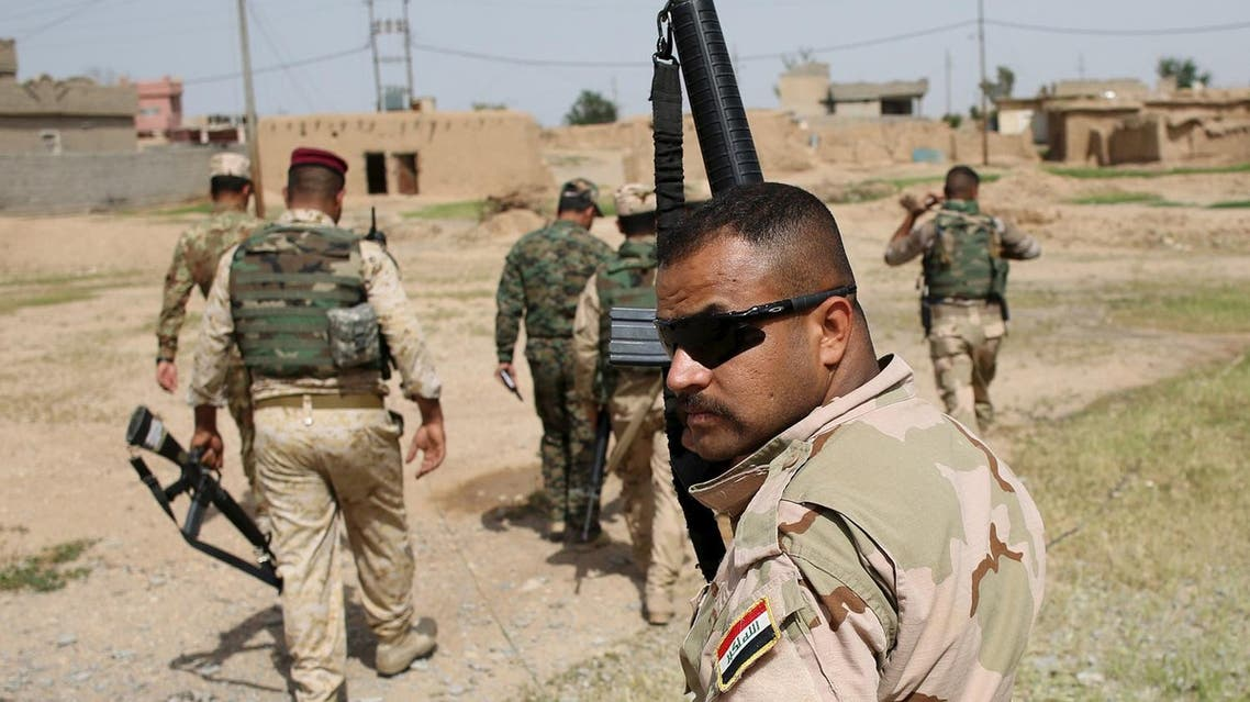 Iraqi soldier holds up his rifle as he walks with other soldiers in a village of Mahana some 60 km south of Mosul, Iraq, April 28, 2016. REUTERS