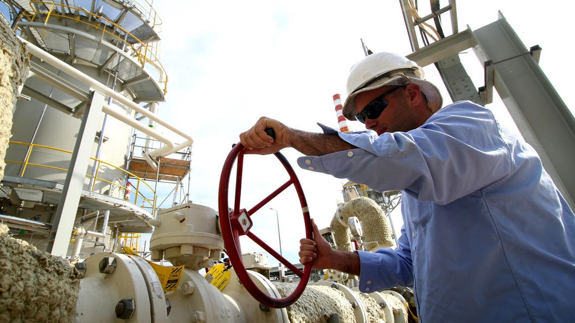 An Iraqi labourer turns a valve at an oil refinery in the newly opened section at the oil refinery of Zubair, southwest of Basra in southern Iraq, on March 3, 2016. (AFP)