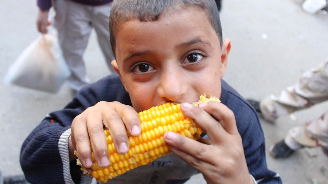 A boy eats maize as people shop ahead of the Muslim festival of Eid-al-Adha in Aleppo October 14, 2013 REUTERS