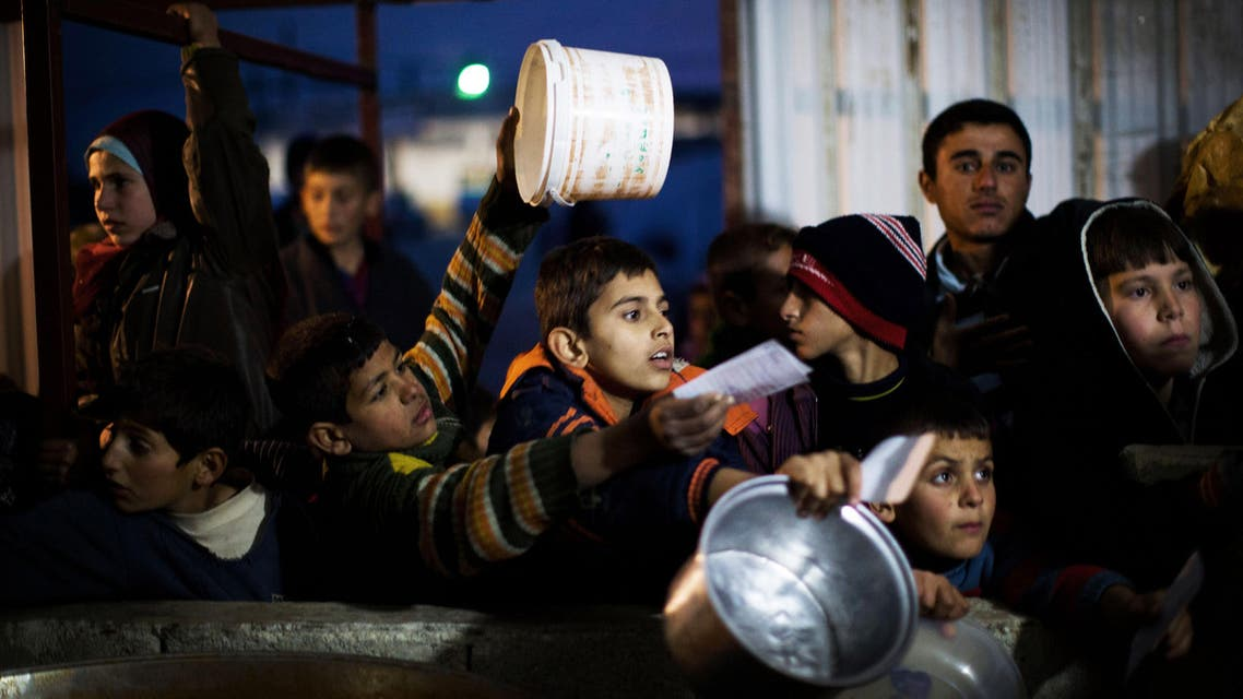 Syrian children wait in line for food distribution at a refugee camp near the Turkish border, in Azaz, Syria, Sunday, Dec. 9, 2012. (AP)
