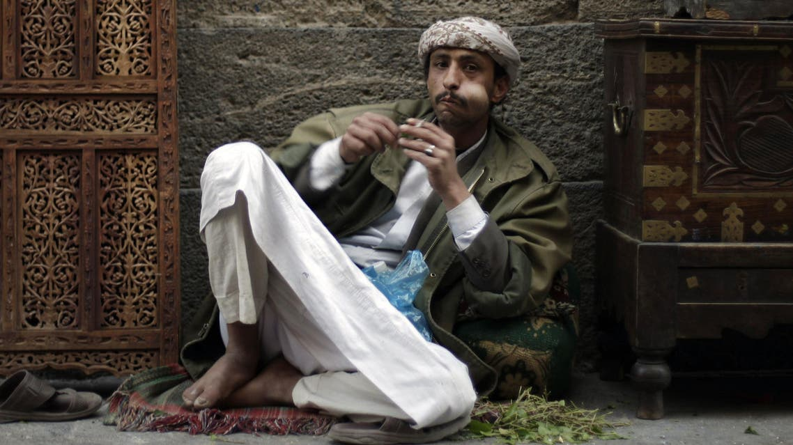 A Yemeni carpenter sits outside his shop as he chews qat, a mildly narcotic plant, in the old city of Sanaa, Yemen, Saturday, Dec. 31, 2011. (AP
