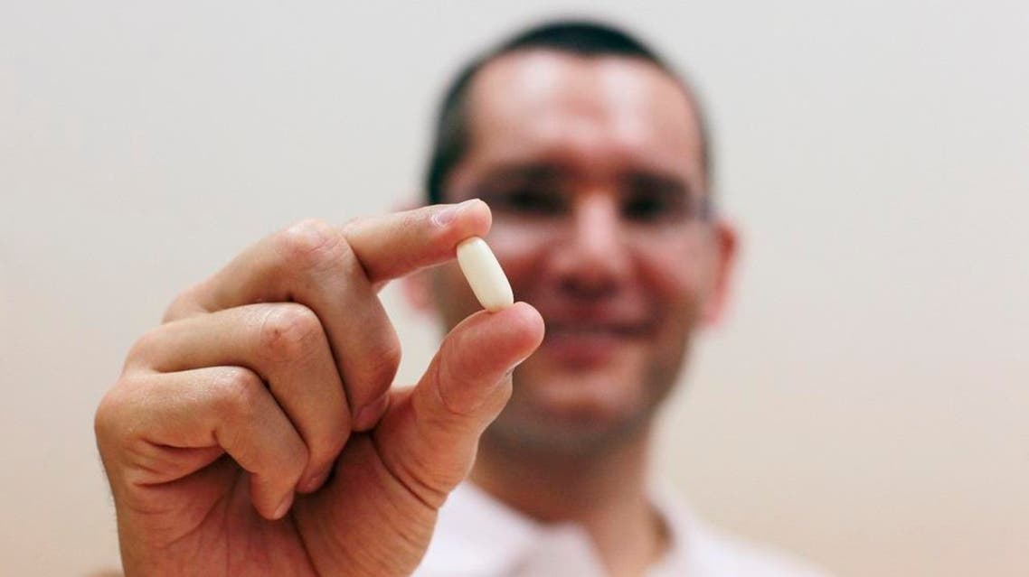 Nadav Kidron, CEO of Oramed Pharmaceuticals, shows an insulin pill as he poses for a photo at the company's offices in Jerusalem September 29, 2013. Reuters/Baz Ratner