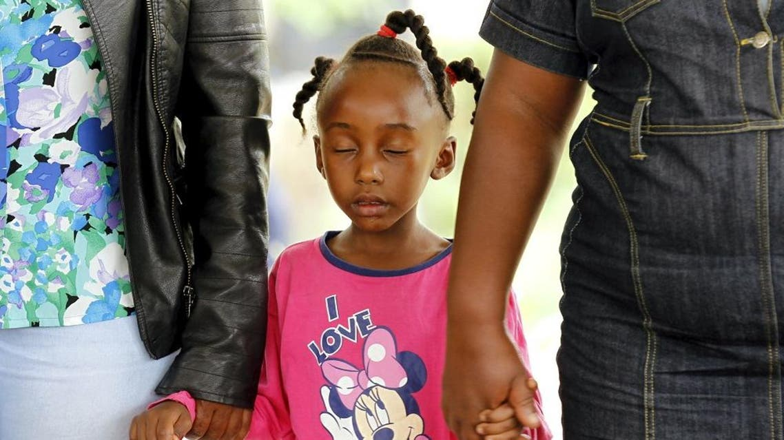 A girl holds hands with parents and relatives in prayers to commemorate the first anniversary of the attack by gunmen on Garissa University College, in Kenya's capital Nairobi, April 2, 2016 (Reuters)