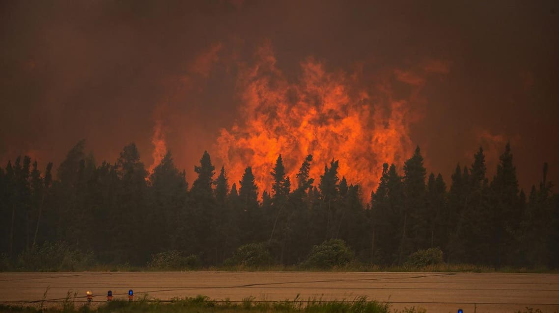 In this July 5, 2015 photo, flames rise from a wildfire near La Ronge, Saskatchewan. Canadian soldiers arrived Tuesday, July 7 to help battle raging wildfires where about 13,000 people have been evacuated in recent days. (Corey Hardcastle/Ministry of the Environment/Government of Saskatchewan via AP)
