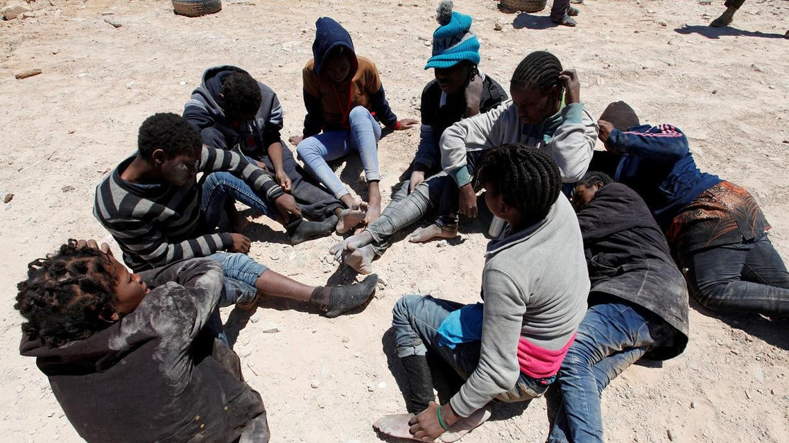 Migrants, who attempted to flee the Libyan coast to head to Europe, are seen sitting in a group after being detained at the coast guard center in the coastal city of Tripoli, Libya. (Reuters)