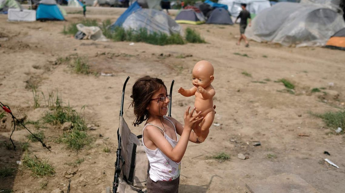 A girl plays with a baby toy at a makeshift camp for refugees and migrants at the Greek-Macedonian border near the village of Idomeni, Greece, May 11, 2016. REUTERS