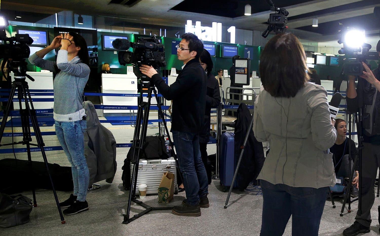 TV crews report near the EgyptAir desk at Charles de Gaulle airport in Paris. (Reuters)