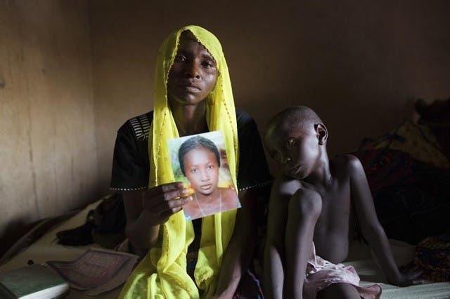 والدة احدى التلميذات المخطوفات من قبل بوكو حرام تحمل صورتها