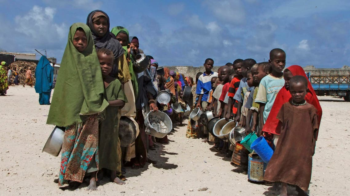 Holding their pots Somali children from southern Somalia, lineup to receive cooked food in Mogadishu, Somalia, Monday, Aug. 15, 2011. AP