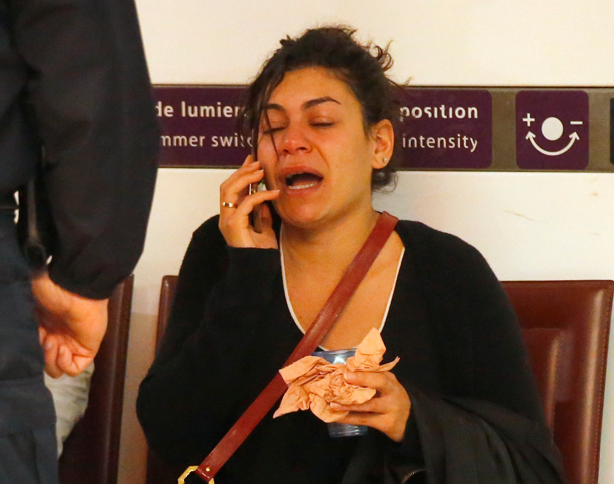 A relative of the victims of the EgyptAir flight 804 reacts as she makes a phone call at Charles de Gaulle Airport outside of Paris, Thursday, May 19, 2016.