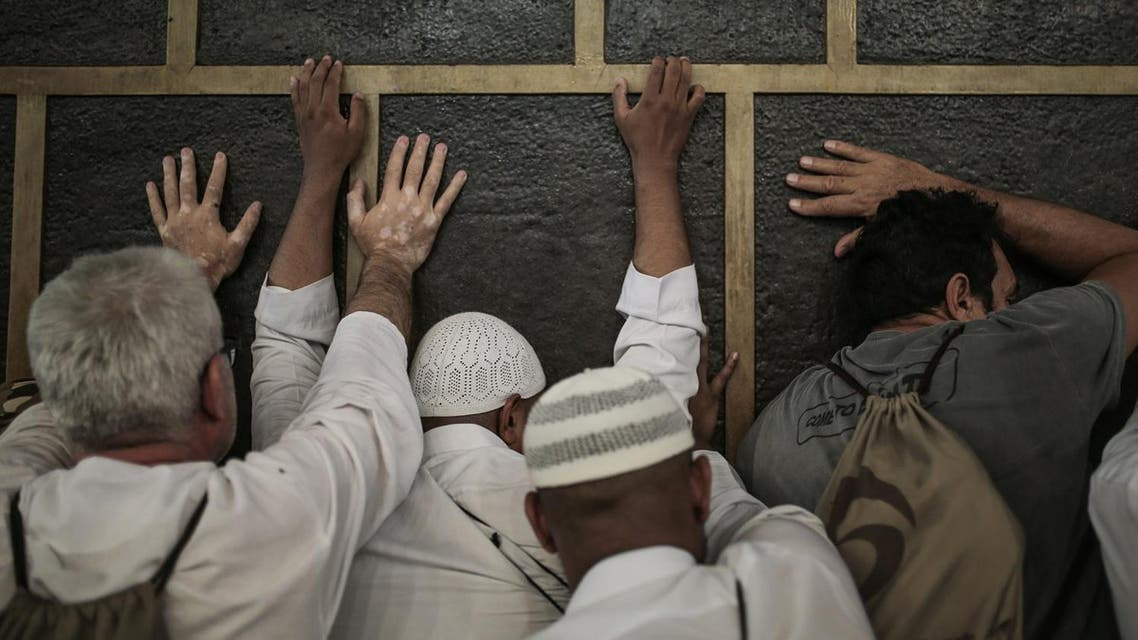 Muslim pilgrims pray while touching the Kaaba, the cubic building at the Grand Mosque in the Muslim holy city of Makkah. (File photo: AP)