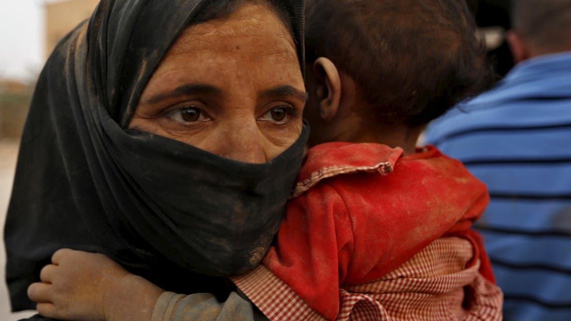 A Syrian refugees wwoman covered with dust carrys her daughter after her arrival at the Trabeel border, after she crossed into Jordanian territory with her family, near the northeastern Jordanian border with Syria, and Iraq, near the town of Ruwaished, 240 km (149 miles) east of Amman September 10, 2015. (Reuters)