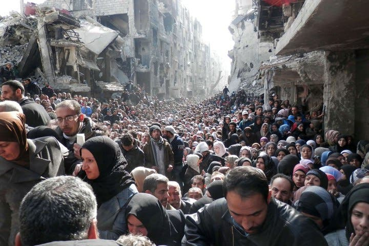 Pictured Desperate refugees queue for food at camp south of the Syrian capital Damascus.  (AFP)