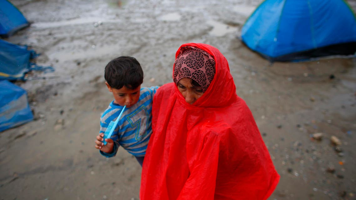 A refugee woman carrying her child walks under heavy rainfall at a makeshift camp for migrants and refugees at the Greek-Macedonian border near the village of Idomeni, Greece, May 21, 2016. (Reuters)