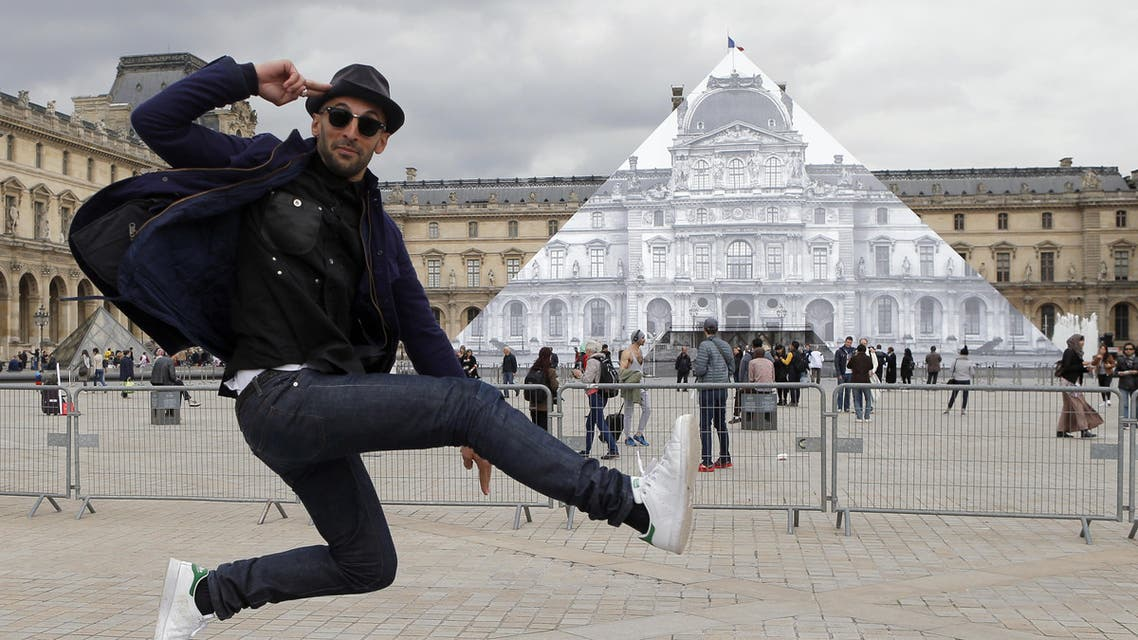 Street artist JR poses in front the Louvre Pyramid in Paris, Tuesday, May 24, 2016. ap