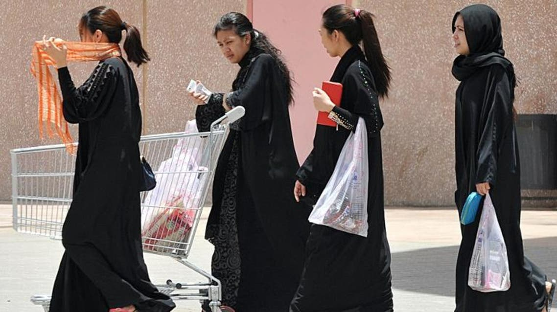 Filipina maids carry shopping bags as they walk out of a mall in Riyadh, on June 12, 2013. (AFP)