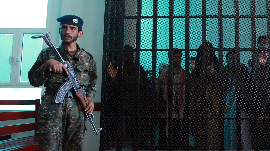 A Yemeni security officer guards prisoners at a court during a hearing at the appeals court in the Yemeni capital Sanaa on February 03, 2015. afp