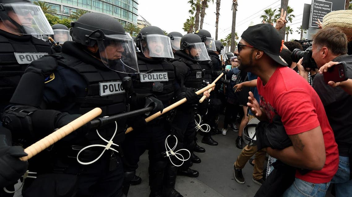 Dozens of police officers in riot gear stood between the two groups and at one point moved in to force the crowd to leave the area around the convention center. (AFP)