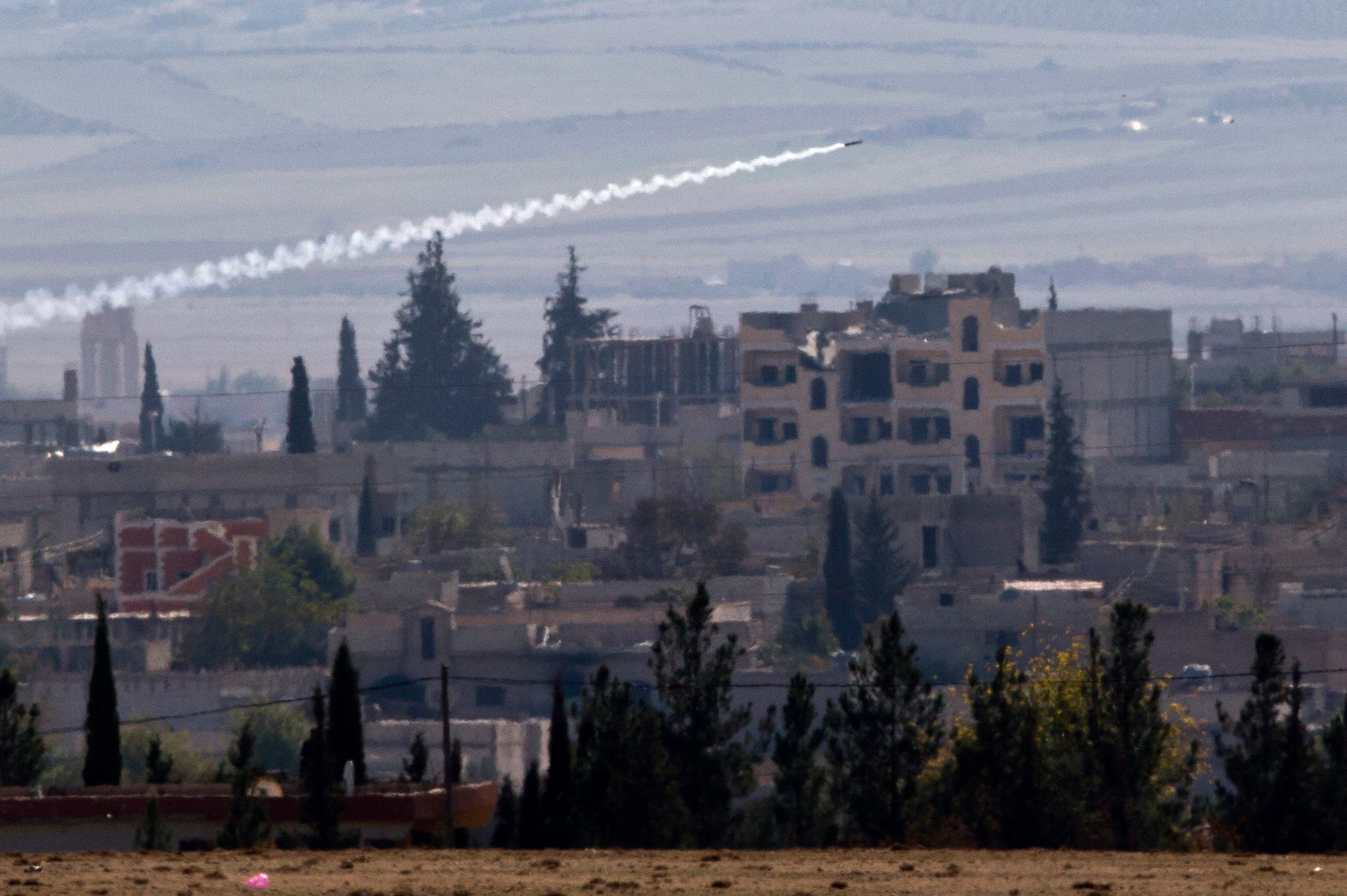 A missile is fired from Islamic State positions in Kobani, seen from a hilltop outside Suruc, on the Turkey-Syria border Thursday, Nov. 6, 2014. Kobani, also known as Ayn Arab, and its surrounding areas, has been under assault by extremists of the Islamic State group since mid-September and is being defended by Kurdish fighters. (AP