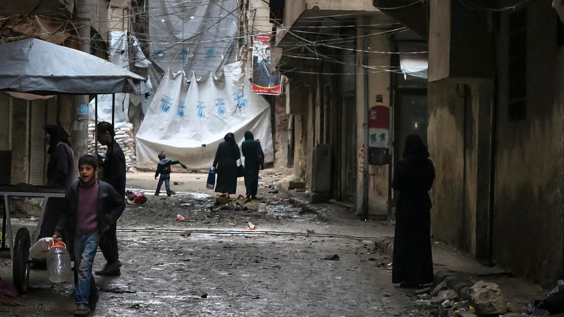 In this Thursday, Feb. 11, 2016 file photo, civilians walk through a street with large tarps are hung in between building to limit the view of regime snipers in Aleppo, Syria.