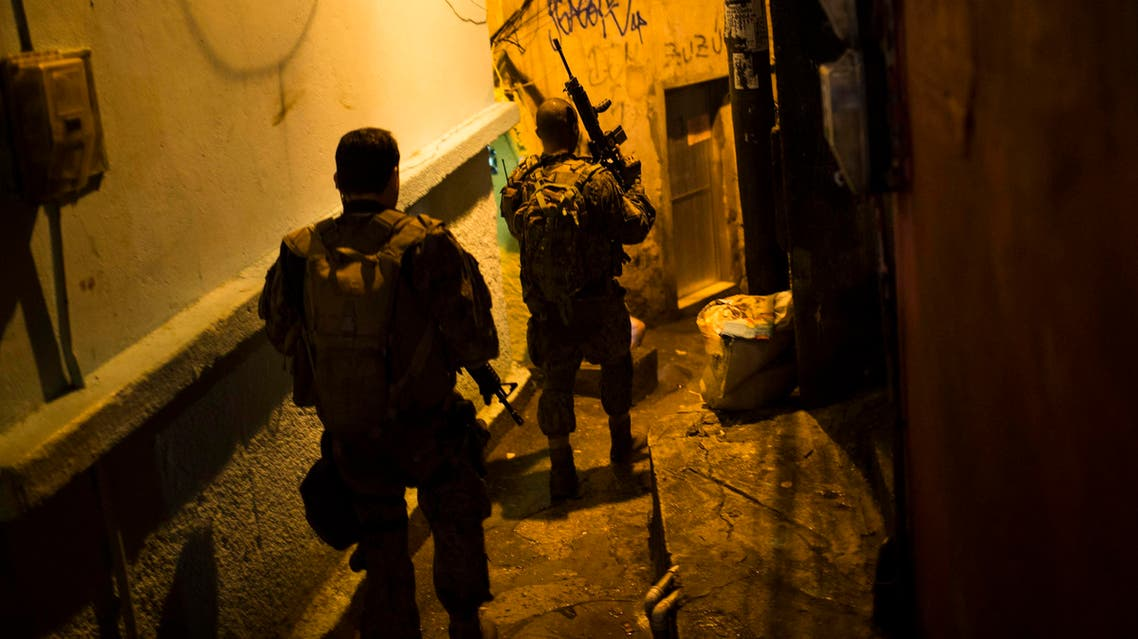 Police officers walk in an alley during a police operation at Rocinha slum in Rio de Janeiro, Brazil, Friday, May 20, 2016. (ap)