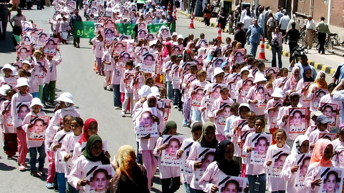 Hundreds of Egyptian girls carry posters showing Badour Shaker, who died earlier this month while being circumcised in an illegal clinic in the southern city of Maghagha, Egypt, during a rally against circumcision in Assiut, Egypt, Thursday July 5, 2007.