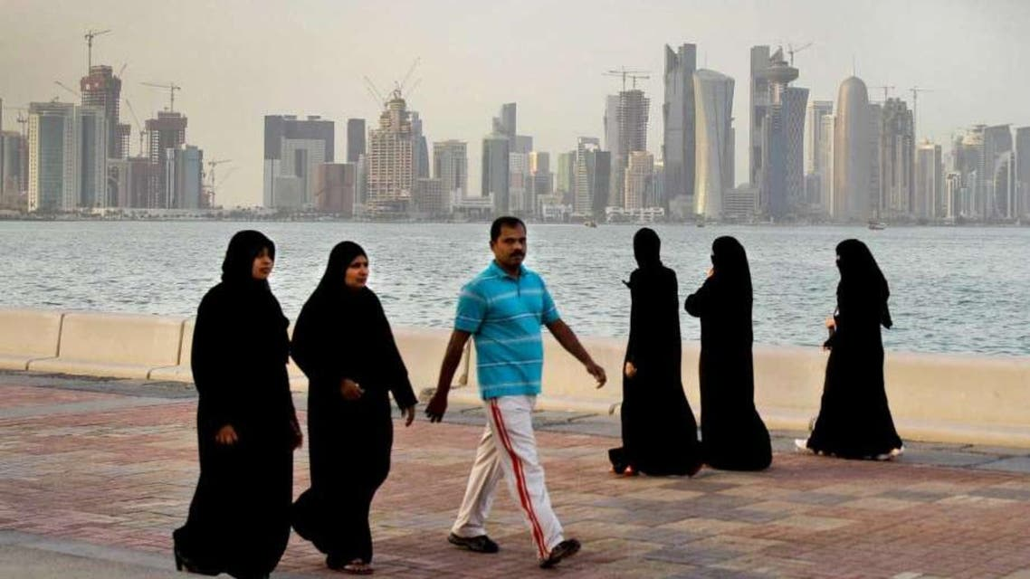 In this Saturday, April 7, 2012 file photo, with the new high-rise buildings of downtown Doha, background, Qatari women and a man walk by the sea in Doha, Qatar. (AP)