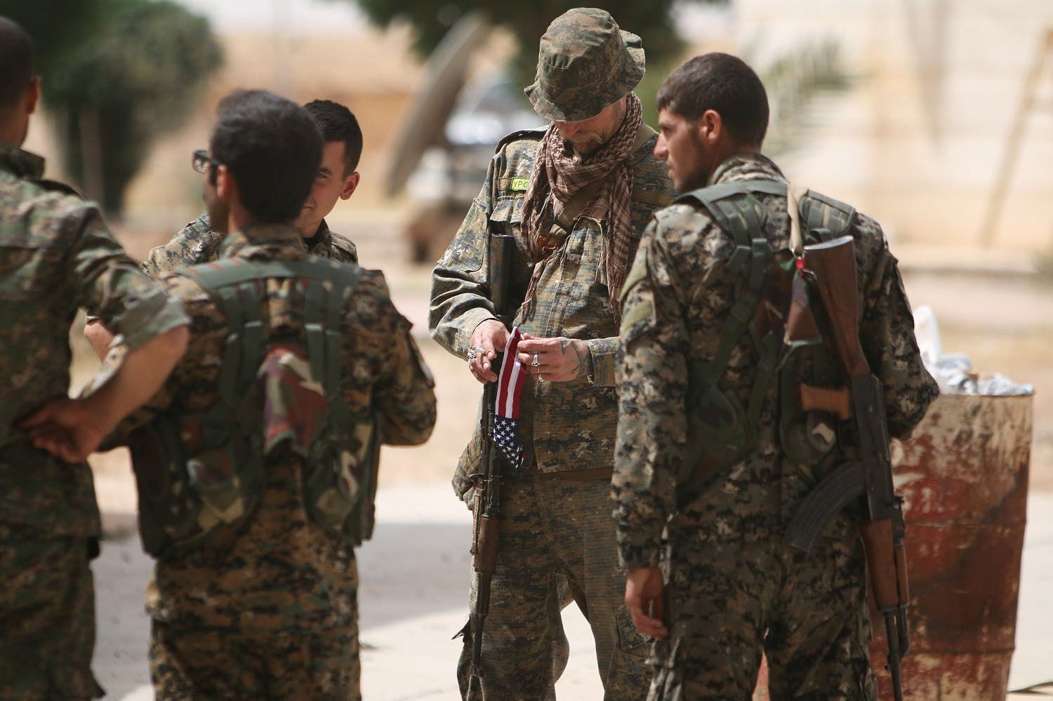 A U.S. fighter, who is fighting alongside with Syria Democratic Forces (SDF), carries his national flag as he stands with SDF fighters in northern province of Raqqa, Syria May 27, 2016. REUTERS