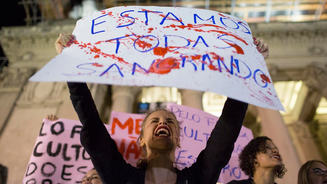 """In this May 27, 2016 photo, a woman shouts holding a banner that reads in Portuguese """"We're all bleeding"""" as she protests the gang rape of a 16-year-old girl in Rio de Janeiro, Brazil. AP"""
