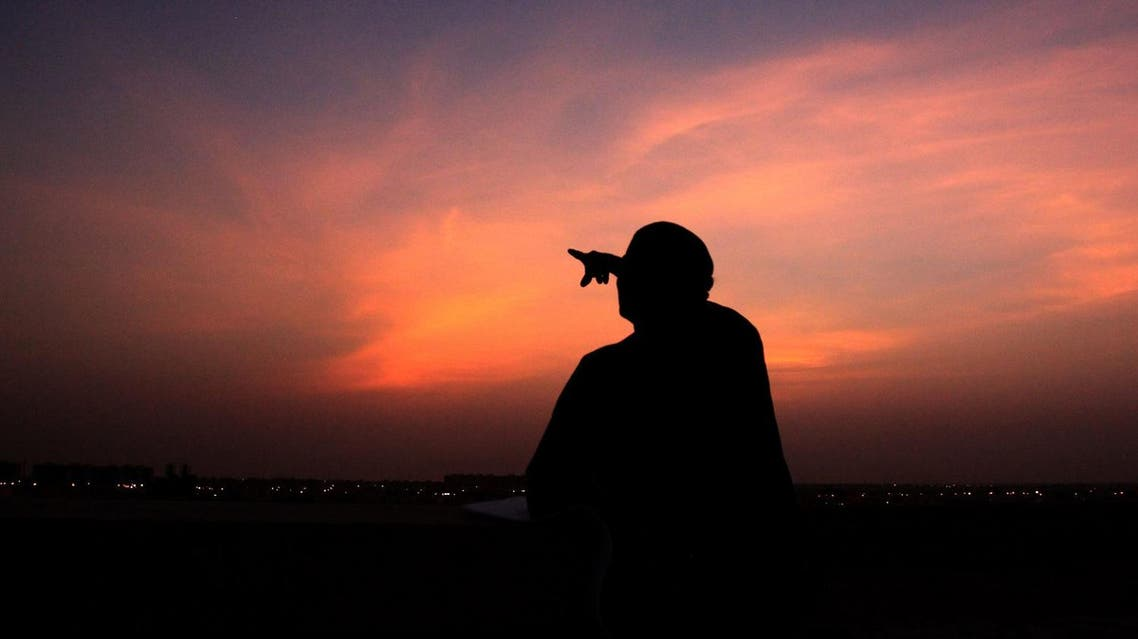 A Bahraini man points skyward at dusk Tuesday, Aug. 10, 2010, in Hamad Town, Bahrain, towards where a slim crescent moon should be visible to indicate the start of the Islamic holy month of Ramadan. (File photo: AP)