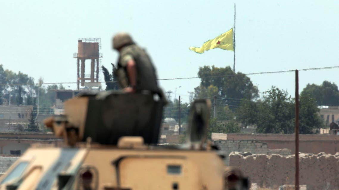a Turkish soldier on an armoured personnel carrier watches as in the background a flag of the Kurdish People's Protection Units, or YPG, is raised over the city of Tal Abyad, Syria, Tuesday, June 16, 2015. ap