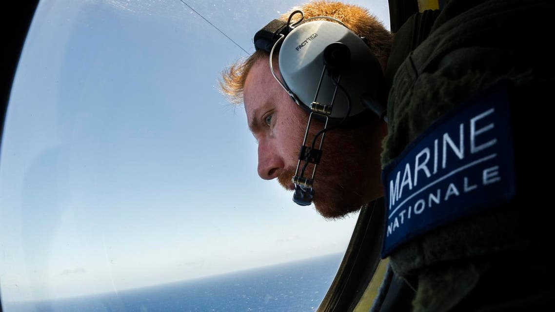 A French solider aboard an aircraft looking out a window during searches for debris from the crashed EgyptAir flight MS804. (AFP)