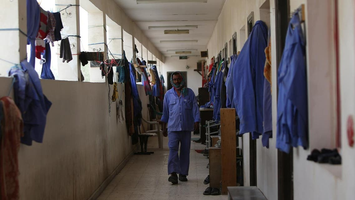 An Indian labourer walks amidst uniforms hanging outside rooms at a private camp housing foreign workers in Doha. (File photo: AFP)