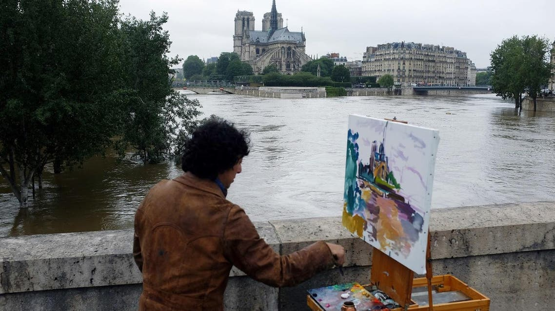 A man paints Notre Dame Cathedral surrounded by the flooding Seine river in Paris, France (Photo: Jerome Delay/AP)