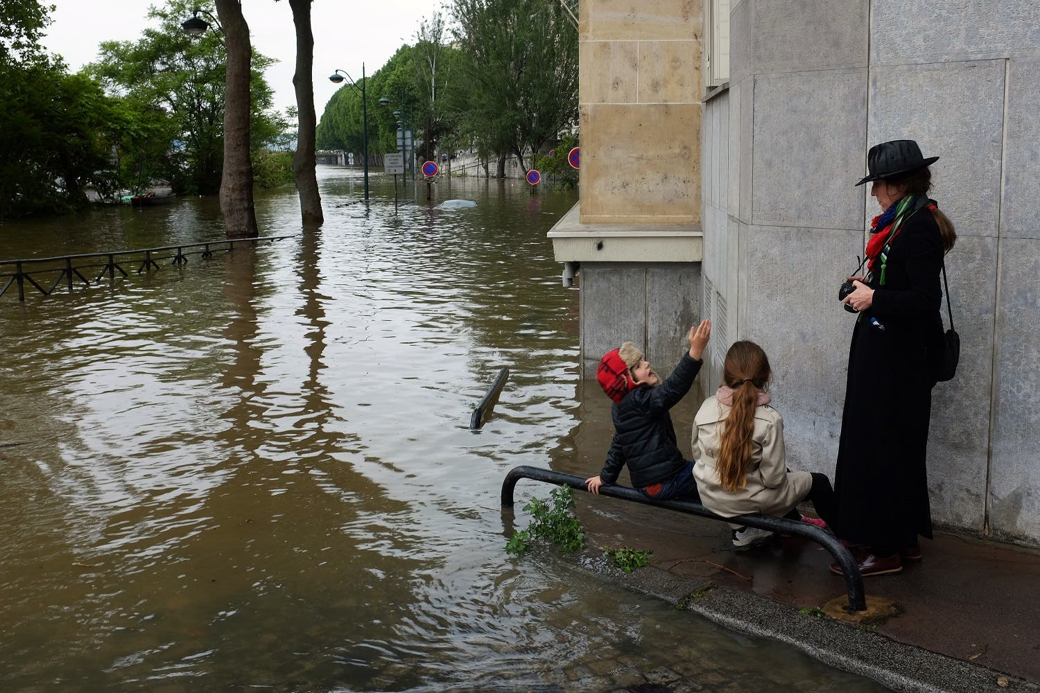 A family visits the flooded banks of the Seine river near the Eiffel Tower in Paris, France (Photo: Jerome Delay/AP)
