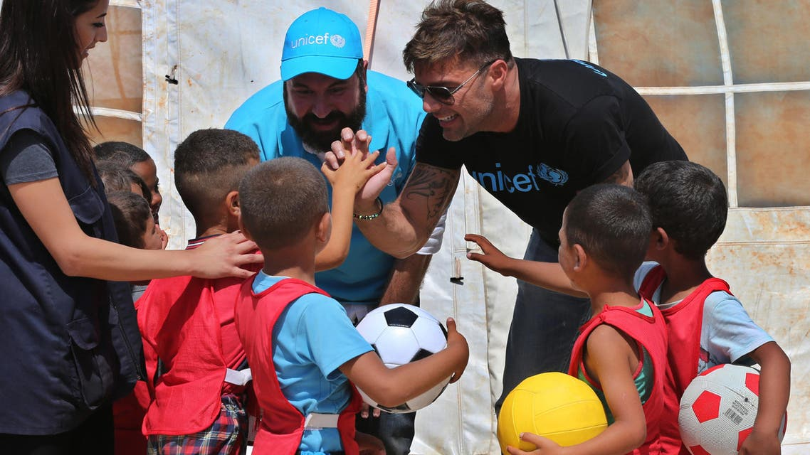 In this picture taken on Thursday June 2, 2016, Ricky Martin, right, the world-renowned singer and UNICEF goodwill ambassador, cheers with Syrian children during his visit to an informal Syrian refugee camp, in Minnieh, near the northern city of Tripoli, Lebanon. AP