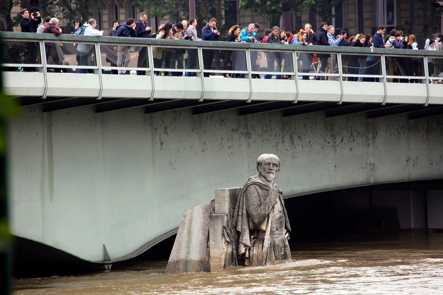 People looking at the floods stand on the Alma bridge by the Zouave statue which is used as a measuring instrument during floods in Paris, France Friday June 3, 2016. (Photo: AP)