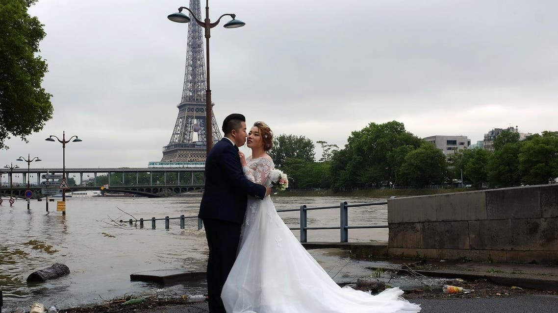 A Chinese couple have their wedding photograph taken on the flooded banks of the Seine river in front of the Eiffel Tower in Paris, France (Photo: Jerome Delay/AP)