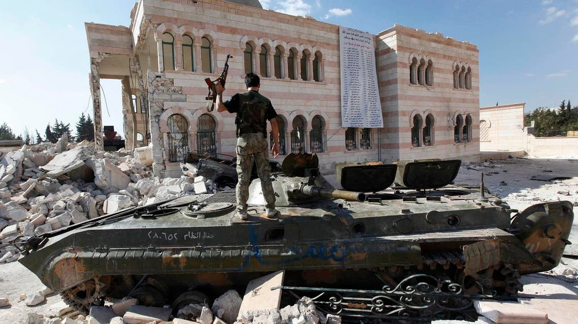 In this file photo taken on Sept. 23, 2012, a Free Syrian Army soldier stands on a damaged Syrian military tank in front of a damaged mosque, which were destroyed during fighting with government forces, in the Syrian town of Azaz, on the outskirts of Aleppo. (AP)