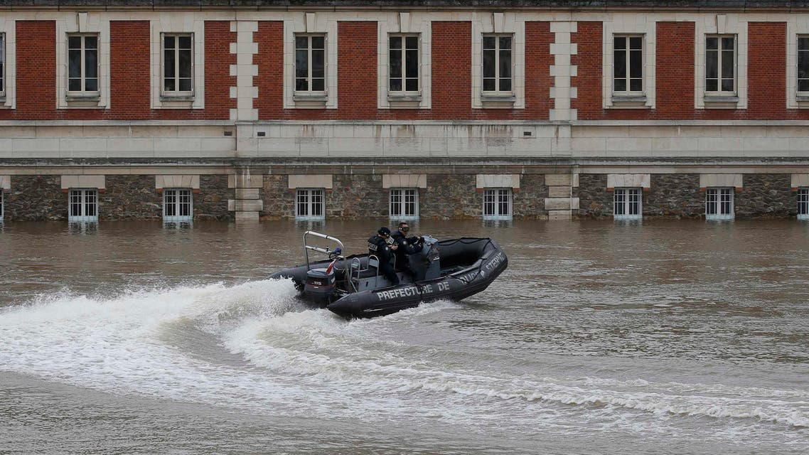 French police officers on a rescue boat patrol past a flooded building on the edge of the Seine River, near Notre-Dame Cathedral, in Paris, June 4, 2016, after days of almost non-stop rain caused flooding in the country. REUTERS/Christian Hartmann