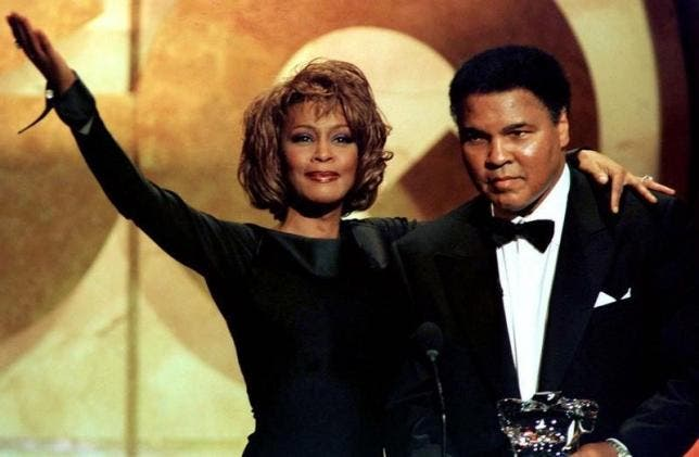 Muhammad Ali is given the Courage Award by singer Whitney Houston at the GQ Men of the Year awards show, October 1998. (Reuters)