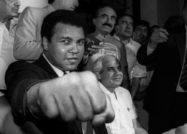 A smiling Muhammad Ali shows his fist to reporters during an impromptu press conference in Mexico City, July 1987.  (Reuters)