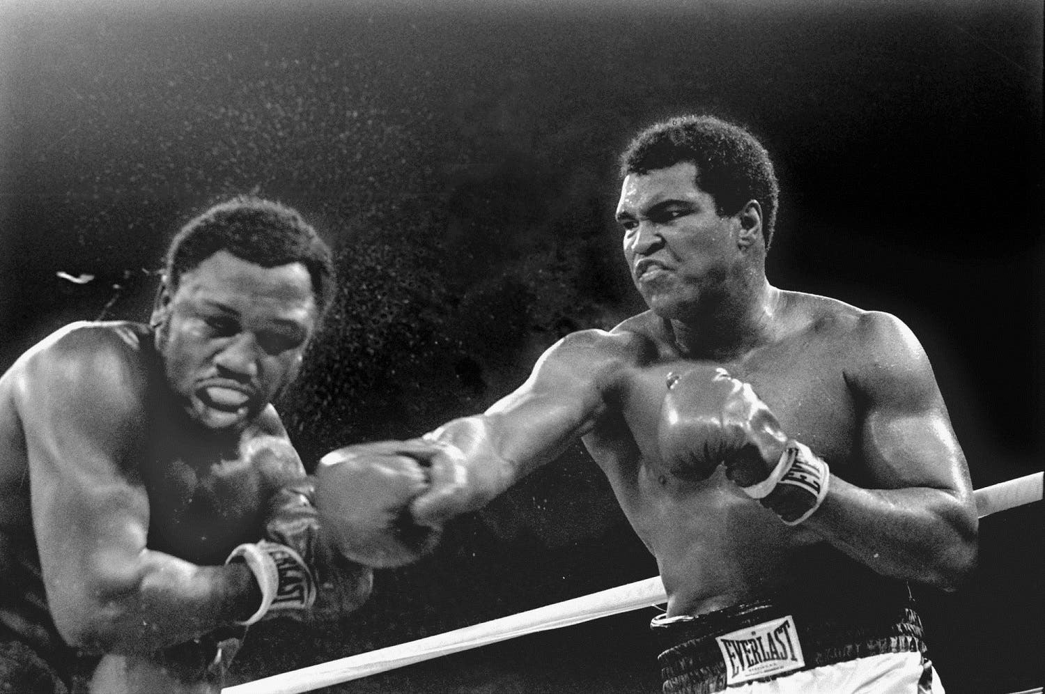 In this Oct. 1, 1975, file photo, spray flies from the head of challenger Joe Frazier as heavyweight champion Muhammad Ali connects with a right in the ninth round of their title fight in Manila, Philippines. Ali, the magnificent heavyweight champion whose fast fists and irrepressible personality transcended sports and captivated the world, has died according to a statement released by his family Friday, June 3, 2016. He was 74. (AP)