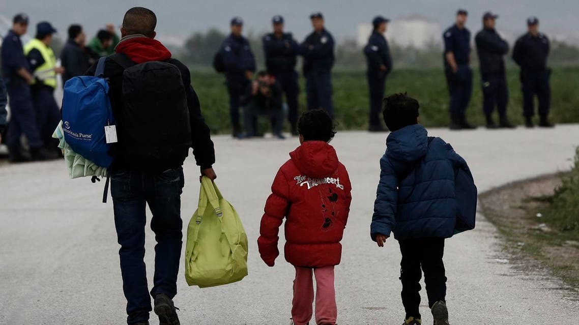 Refugees carry their belongings in front of riot policemen during a police operation at a refugee camp at the border between Greece and Macedonia, near the village of Idomeni, Greece, 24 May 2016. REUTERS
